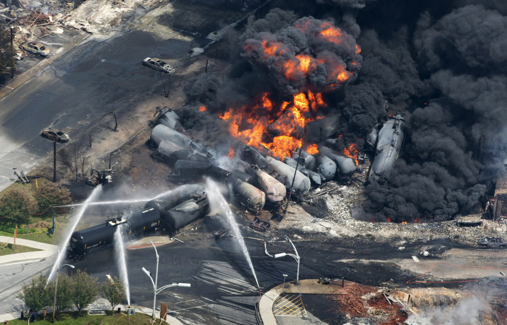 Smoke rises from flaming railway cars that were carrying crude oil after a train derailed in downtown Lac-Megantic, Quebec, in July 2013. The top executive of Central Maine and Quebec Railway said Friday that the company wants to resume oil shipments on the route by January 2016 after track safety improvements are made.