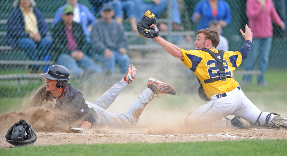 Staff photo by Michael G. Seamans YOU'RE OUTTA HERE: Mt. Blue High School catcher Andrew Pratt, 22, tags out Skowhegan High School's DJ Allen, 22, on Friday.