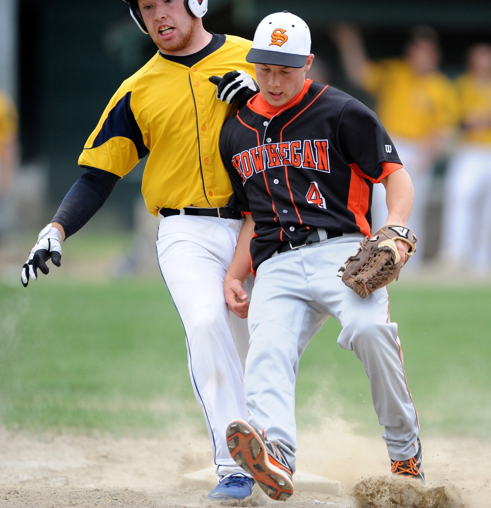 Staff photo by Michael G. Seamans Mt. Blue High School's Andrew Pratt, 22, collides with Skowhegan High School pitcher John Swett, 4, at first base in Farmington on Friday, May 16, 2014. Pratt was safe on the play. Skowhegan defeated Mt. Blue 4-2.