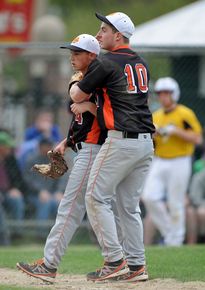 Staff photo by Michael G. Seamans Skowhegan High School's Adam Clukey, 10, celebrates with teammate John Swett, 4, after their 4-2 win over Mt. Blue High School , in Farmington on Friday, May 16, 2014.