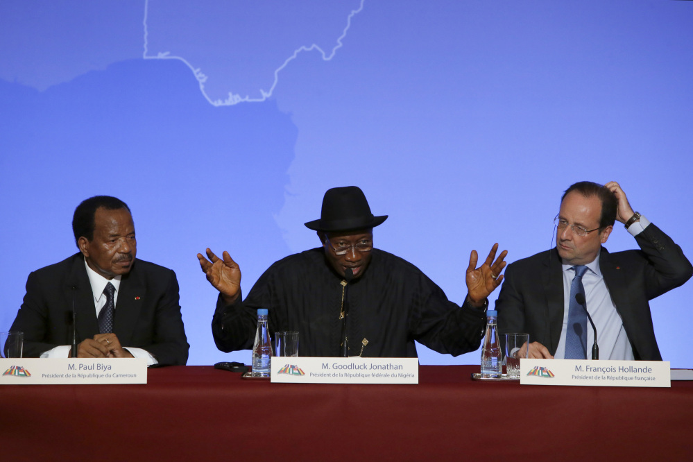 """Nigeria President Goodluck Jonathan, center, answers reporters' questions. He is flanked by Cameroon President Paul Biya, left, and French President Francois Hollande during a news conference ending the """"Paris Summit for Security in Nigeria"""" at the Elysee Palace on Saturday."""