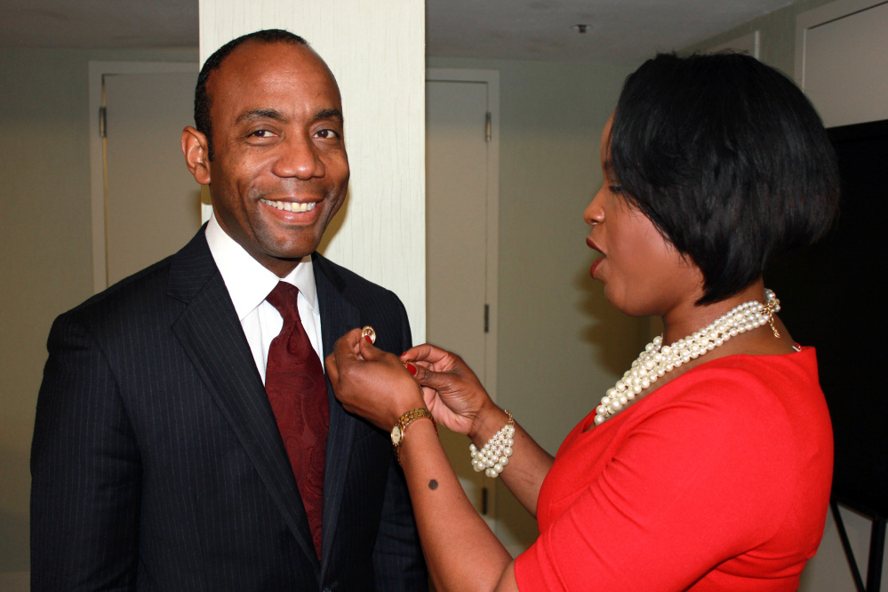 Roslyn Brock, right, chairman of the national board of directors for the NAACP, puts a NAACP pin on new national president and CEO, Cornell William Brooks on Saturday in Fort Lauderdale, Fla.