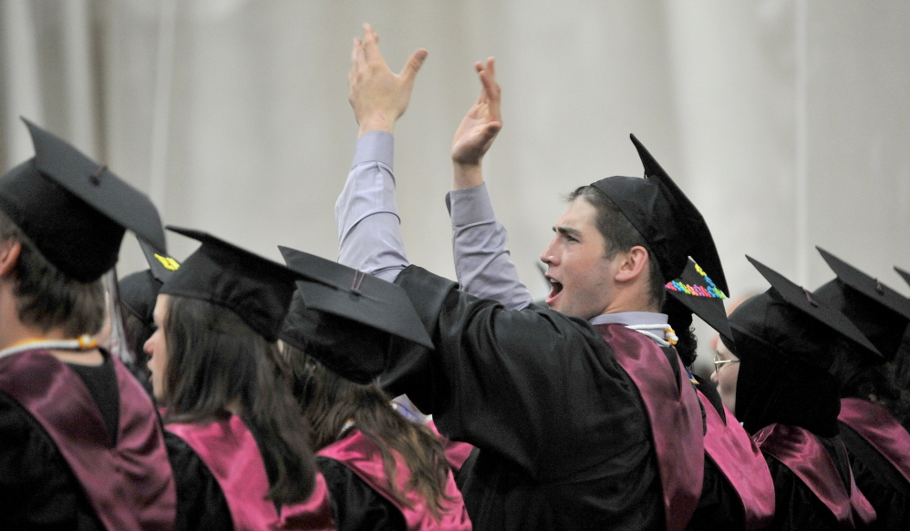 Clap happy: Ben Johnson celebrates on Saturday during the University of Maine at Farmington 2014 commencement ceremony in Farmington.
