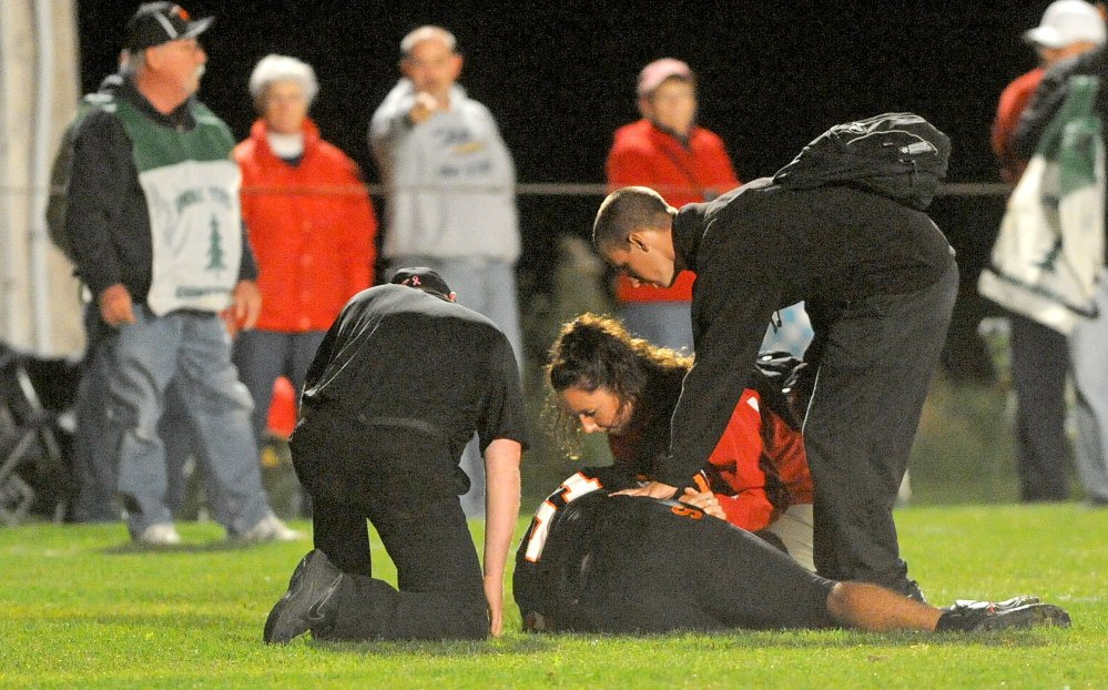 Helping the Injured: Trainers from Cony High School and Skowhegan High School tend to an injured Skowhegan player in Skowhegan Oct. 4, 2013.