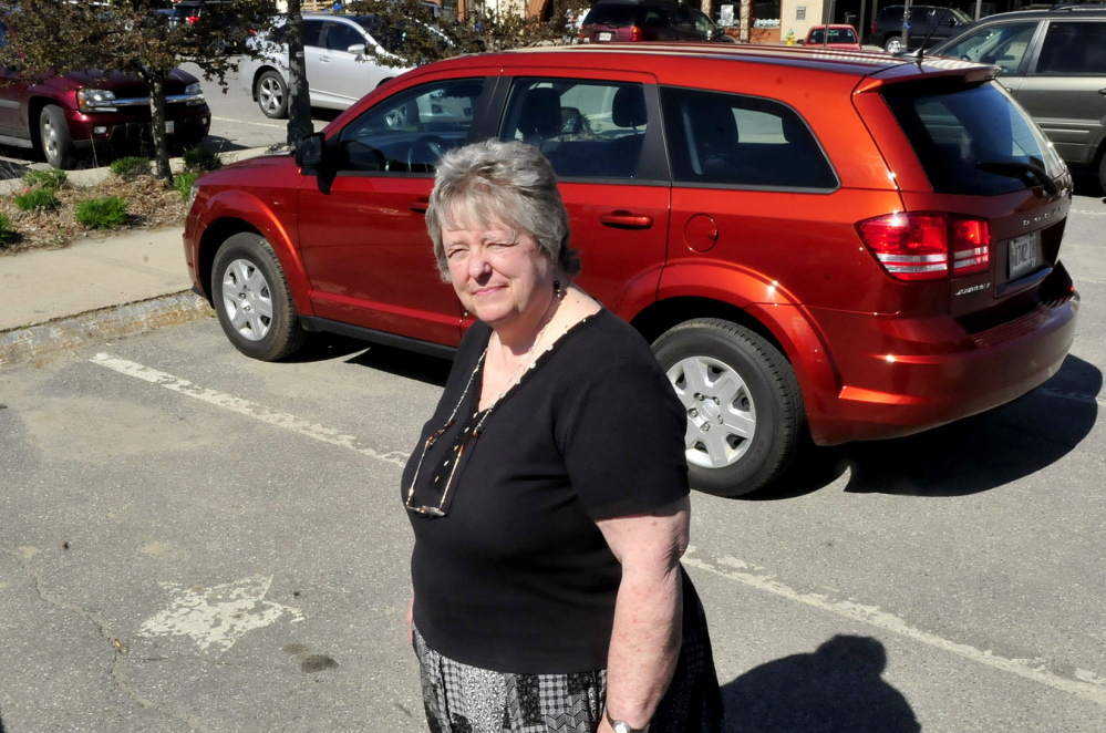 CONCERN: Faye Nicholson, co-executive director of REM in Waterville, stands beside a parking spot marked with a star for all-day parking in The Concourse. Nicholson thinks Waterville's farmers market, which occupies part of the parking lot on Thursdays, would better serve shoppers and people who need parking spaces if it were moved to nearby Head of Falls along the Kennebec River.
