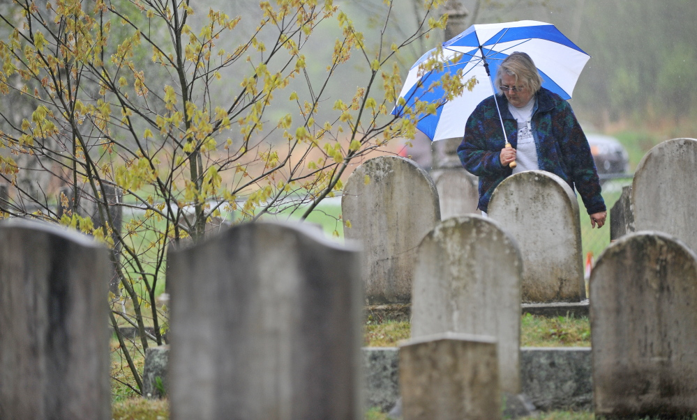 It's set in stone: Elsie Bonney, of Bethel, reads the headstones Saturday at Frederic Cemetery in Starks. The Maine Old Cemetery Association, which works to preserve old cemeteries, held its annual spring meeting in Starks.