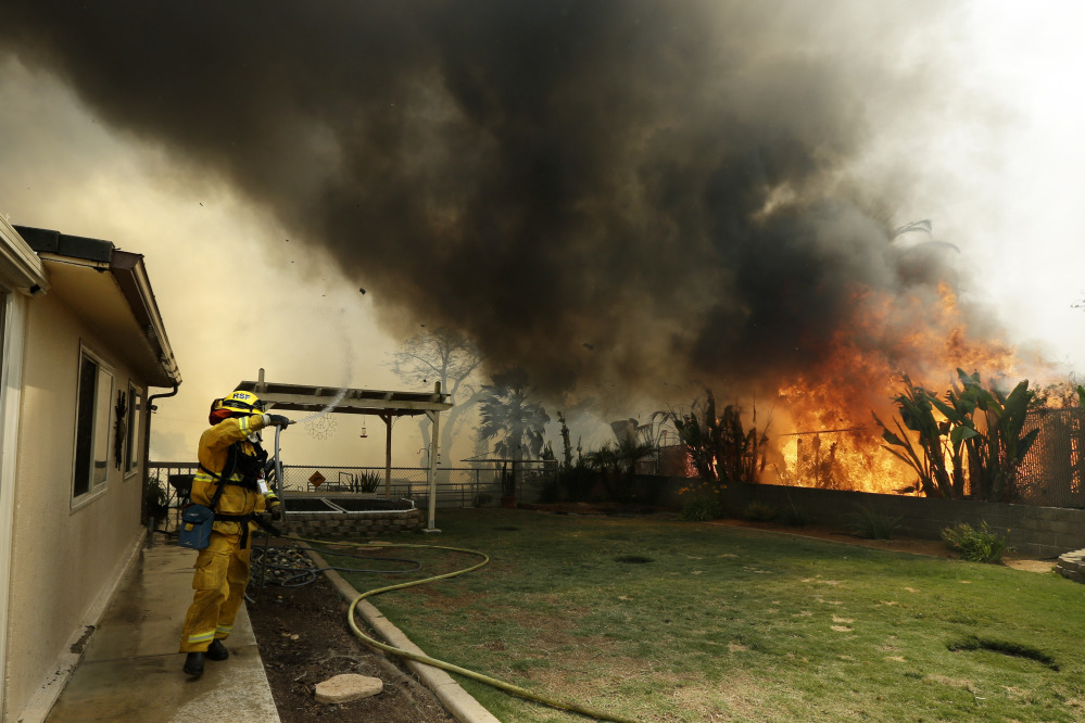 A firefighter moves away as shifting winds bring a plume of smoke from a wildfire Thursday in Escondido, Calif.