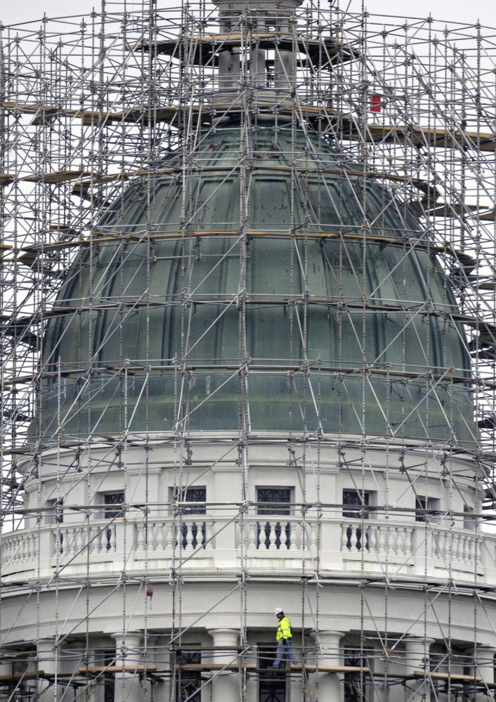 A worker walks on the staging at the State House dome in Augusta on Monday. Lawmakers are discussing how to use the dome's copper.