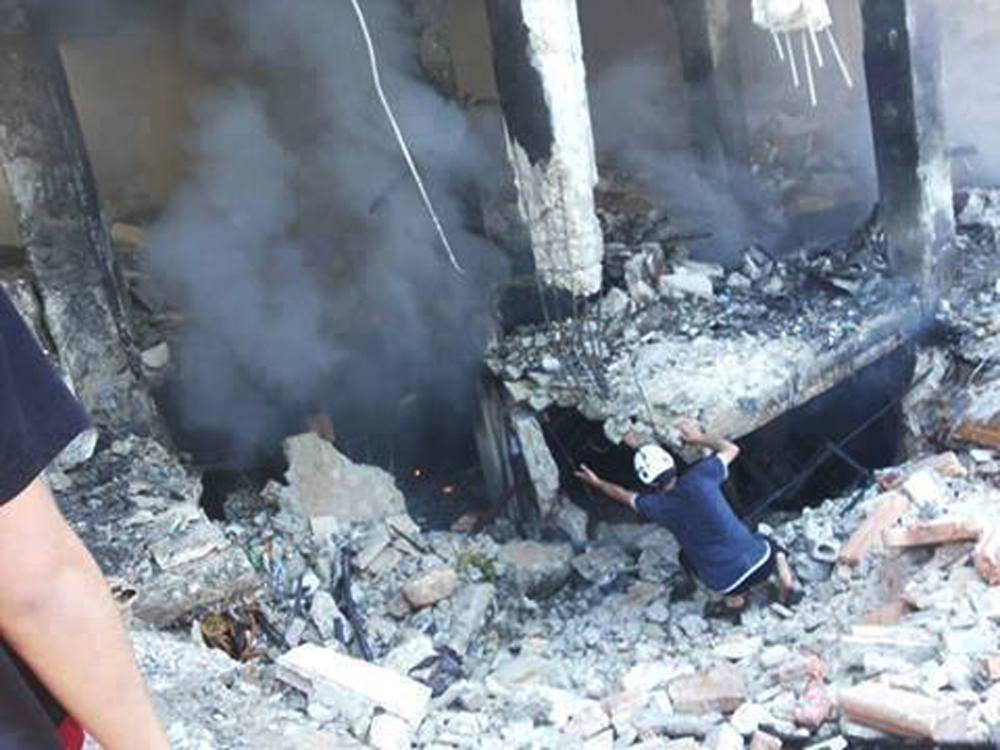 This photo provided by an anti-Bashar Assad activist group Edlib News Network (ENN), which has been authenticated based on its contents and other AP reporting, shows a Syrian man checking a damaged building at the scene where a car bomb exploded outside a mosque at Binnish town, in Idlib province, northern Syria, Friday.