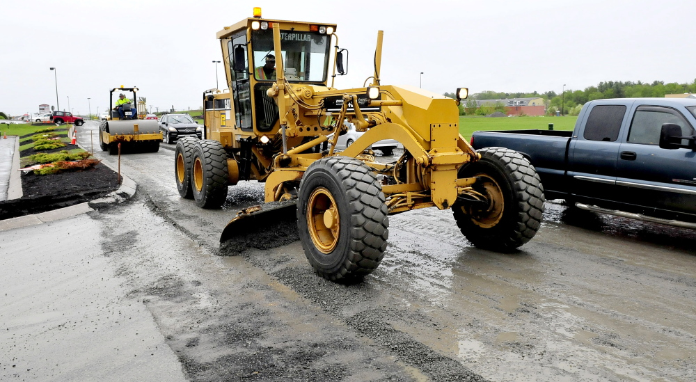 ROAD RAGE: Motorists drive around workers operating a grader and roller resurfacing Waterville Commons Drive Monday. Road conditions and heavy traffic last Saturday contributed to major congestion, causing delays and road rage.