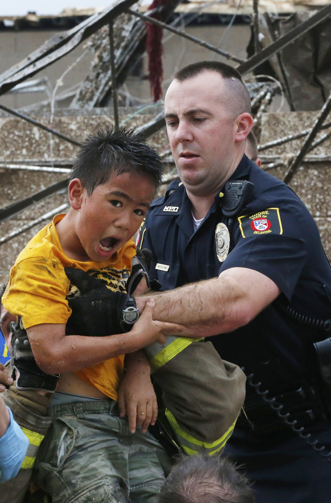 Kai Heuangpraseuth, left, is pulled from beneath a collapsed wall at the Plaza Towers Elementary School after a tornado on May 20, 2013, in Moore, Okla. Heuangpraseuth will return to a new Plaza Towers Elementary in the fall, built on the same spot where seven of his schoolmates died.