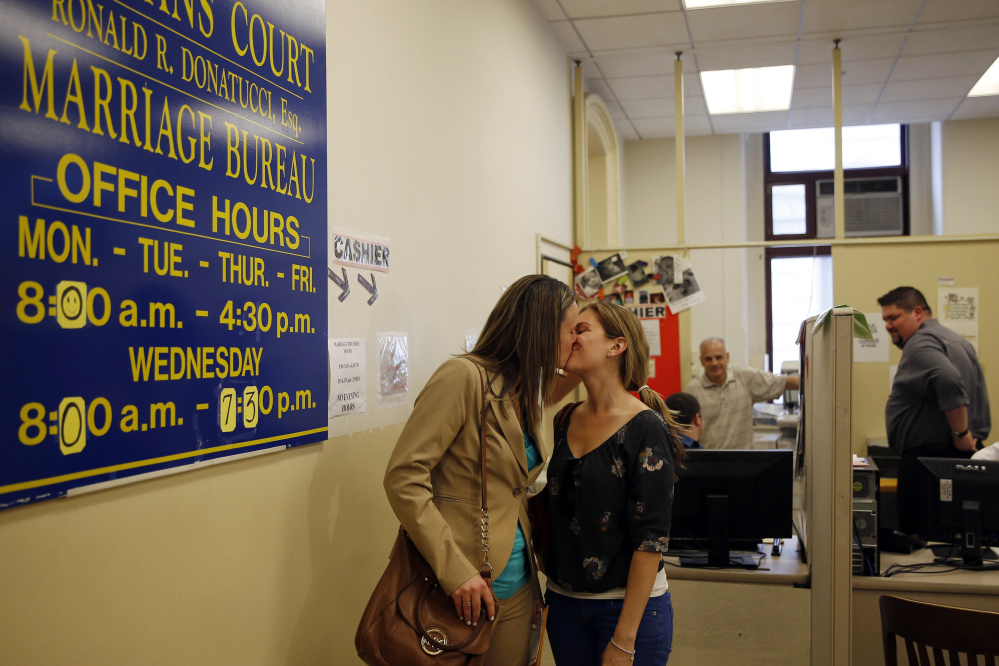 Ashley Wilson, left, and Lindsay Vandermay, right, both 29, kiss after getting their marriage license at the Philadelphia Marriage Bureau in City Hall, Tuesday, May 20, 2014, in Philadelphia. Pennsylvania's ban on gay marriage was overturned by a federal judge Tuesday.