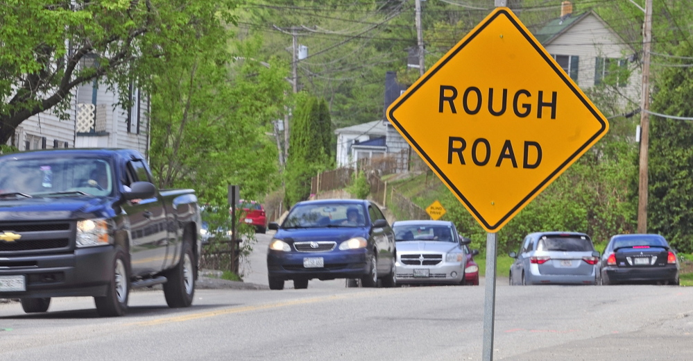 Staff photo by Joe Phelan ROCKY ROAD: Cars drive over potholed road surface on Mount Vernon Avenue near corner of Mill Street on Tuesday.