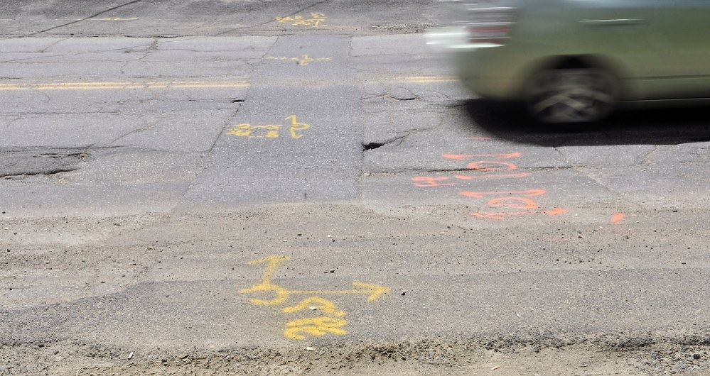 Staff photo by Joe Phelan ROUGH RIDES: Cars drive over potholed road surface on Mount Vernon Avenue near corner of Mill Street Tuesday.
