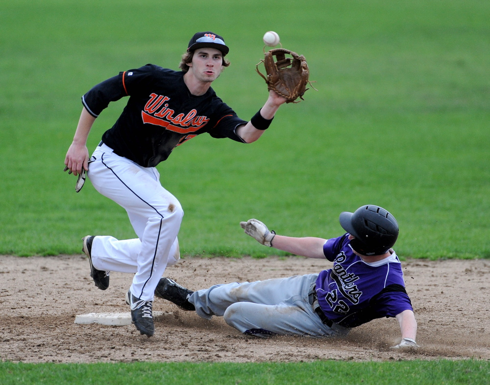 Staff photo by Michael G. Seamans Winslow High School's Alex Berard, 17, is late getting the ball as Waterville Senior High School'sKaleb Kane, 22, slides in to second base on the steal attempt Tuesday.