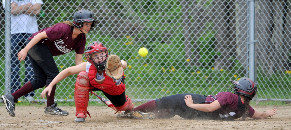 SAFE: Nokomis High School's Sierra Fortin (1) slides safely across home plate ahead of the ball in front of Winslow High School catcher Kiana Richards on Wednesday in Newport. The Warriors won 7-2, improving their record to 12-0.