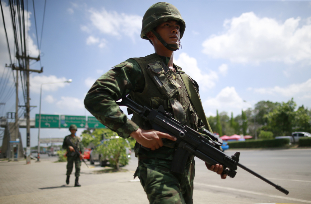 Thai soldiers patrol a road near the rally site for pro-government demonstrators on the outskirts of Bangkok, Thailand, on Thursday. The opponents in Thailand's polarizing political crisis prepared Thursday for a second round of talks mediated by the country's army chief, who says he invoked martial law and then summoned the bitter rivals to try to end six months of turmoil.