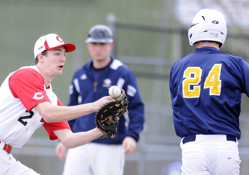 Staff photo by Andy Molloy Cony High School's Mitchell Bonenfant can't hold onto a throw Wednesday while attempting to tag Mt. Blue's Amos Herrin at first base during a baseball match up in Augusta.