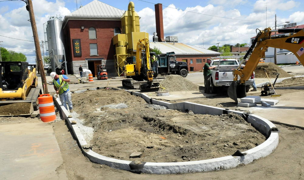 PROGRESS: Workers install granite sidewalk sections and prepare to resurface the parking lot Thursday near the Somerset Grist Mill in Skowhegan as part of a $400,000 grant paying for upgrading the municipal parking lot.