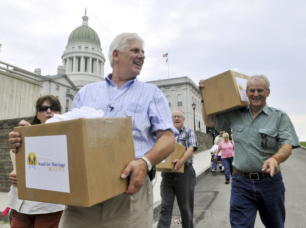 "Bob Emrich, left, is shown delivering signatures collected by Stand for Marriage Maine to the secretary of state. Emrich, who helped run the 2009 and 2012 ballot committees that National Organization for Marriage dollars helped fund, said those donors should be protected. ""People are targeted for harassment for contributing to a cause they believe in,"" he said."