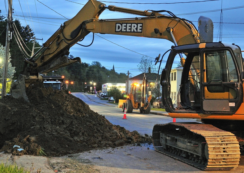 Heavy equipment, heavy task: An excavator frames a front end loader driving through an overnight construction zone Wednesday on Mount Vernon Avenue in Augusta.