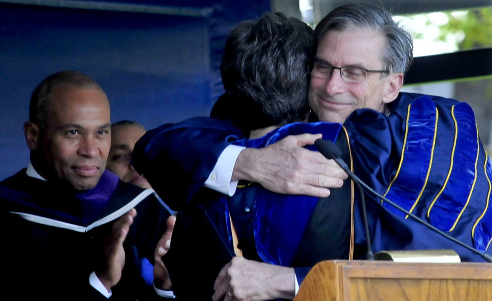 FAREWELL: Retiring Colby College President William Adams hugs Dean of Faculty Lori Kletcher after he received an honorary Doctor of Letters degree during his final commencement at the Waterville college on Sunday. Commencement speaker Massachusetts Gov. Deval Patrick is at left.