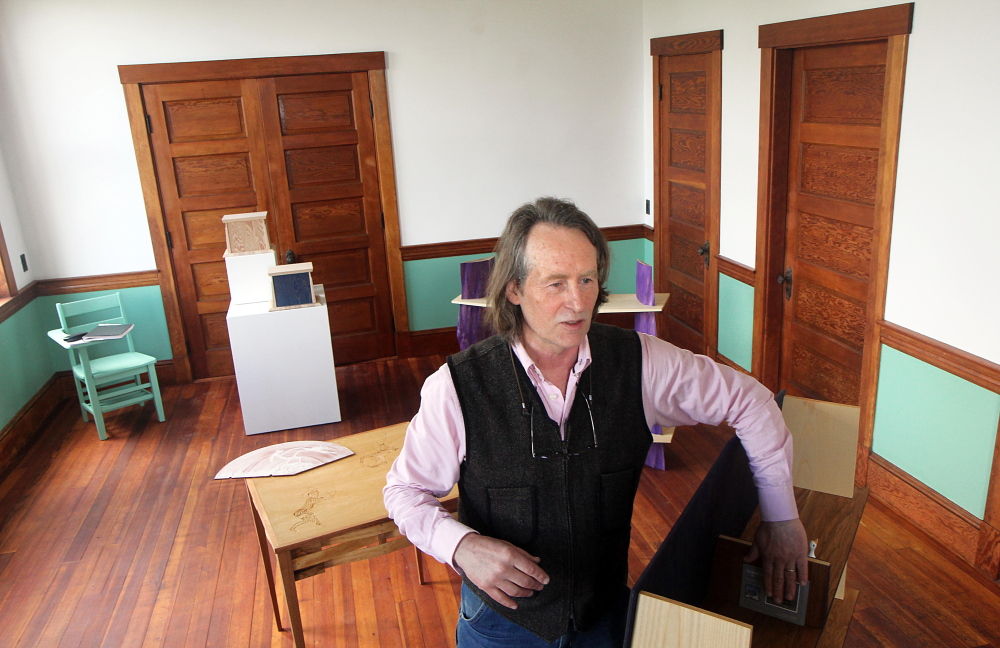 IN THE GALLERY: Dutch woodworker Erik Groenhout describes a literary cabinet on display at his gallery at the old Oddfellows Hall in Mount Vernon on Sunday. Groenhout has slowly been restoring the building since acquiring it in 2011.