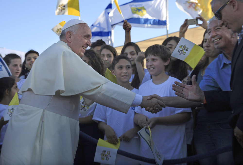 Pope Francis greets Israeli children in Jerusalem on Sunday. The pontiff took a plunge into Mideast politics while on his Holy Land pilgrimage, receiving an acceptance from the Israeli and Palestinian presidents to visit him at the Vatican next month to discuss peace efforts.