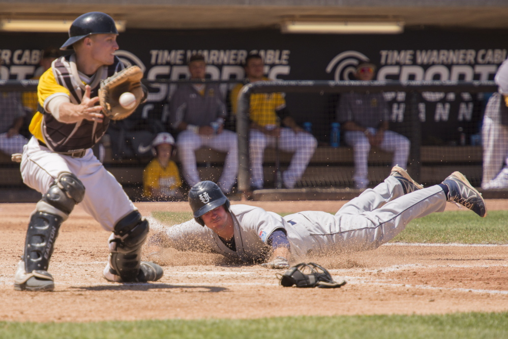 University of Southern Maine's Jake Glauser slides in safe at home for the Huskies' first run of the game during the fifth inning Sunday against Baldwin Wallace in the NCAA Division III baseball championships at Appleton, Wis. USM overcame a 3-0 deficit and avoided elimination with an 11-5 victory.