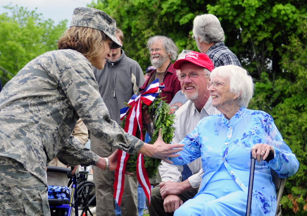 Air Force Reserves Lt. Col. Lorinda Fontaine Farris, left, takes a wreath from Priscilla Berry Stevenson to place it on a memorial to Wayne citizens killed fighting in the first and second World Wars during Memorial Day events Monday in Wayne. Stevenson's late brother Army Capt. J. Ford Berry was kiled in Sicily in WWII. Her son Ford Stevenson is kneeling beside her.