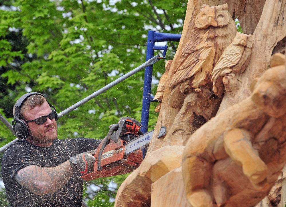 WOOD WORKER: Josh Landry carves a large maple tree Tuesday May 20 on Green Street in Winthrop.