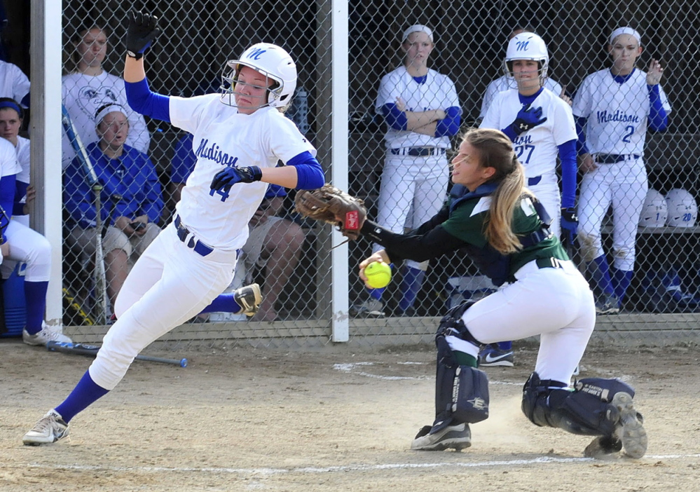Staff photo by David Leaming SAFE: Madison's Cristie Vicneire, left, crosses home plate as Winthrop's catcher Cat Ouellette tries to make the tag during a game Monday in Madison. The Bulldogs won 9-0.