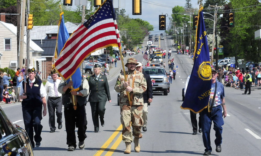 Staff photo by David Leaming ONWARD: The color guard leads the Memorial Day parade in Skowhegan on Monday, May 26, 2014.