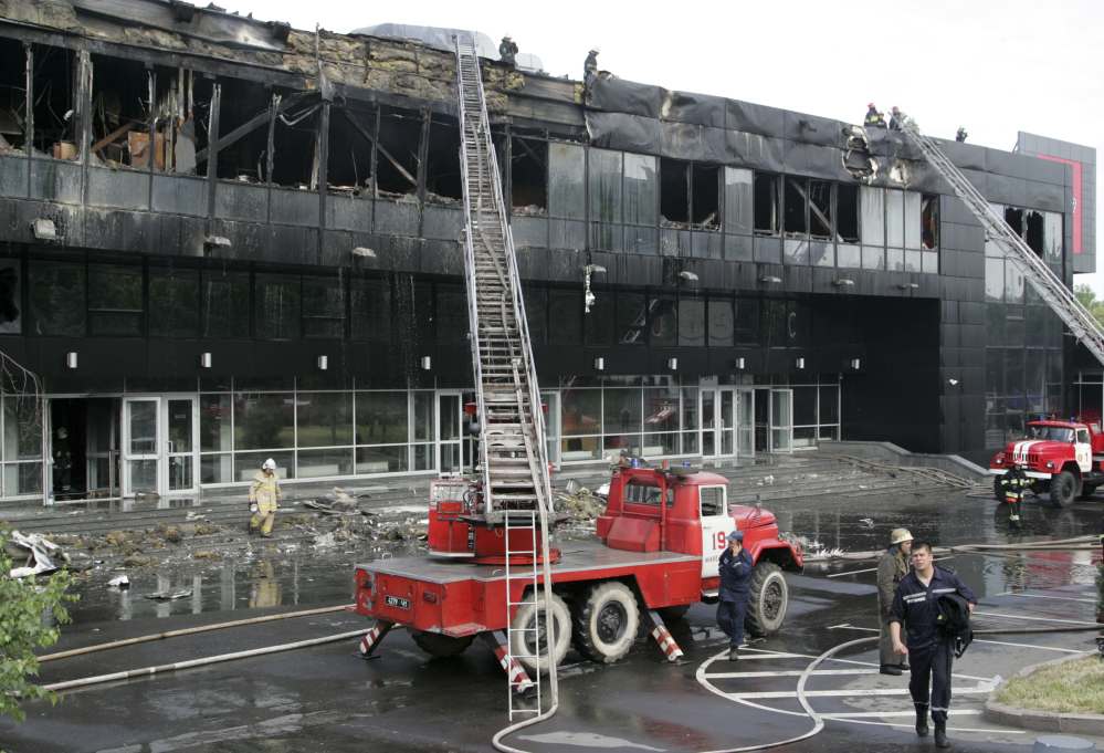 Firefighters work at a burnt ice hockey arena in Donetsk, Ukraine, Tuesday. Early Tuesday, a group of unidentified men stormed Donetsk's main ice hockey arena, which was to host the 2015 world championships and set it ablaze, according to the mayor's office.