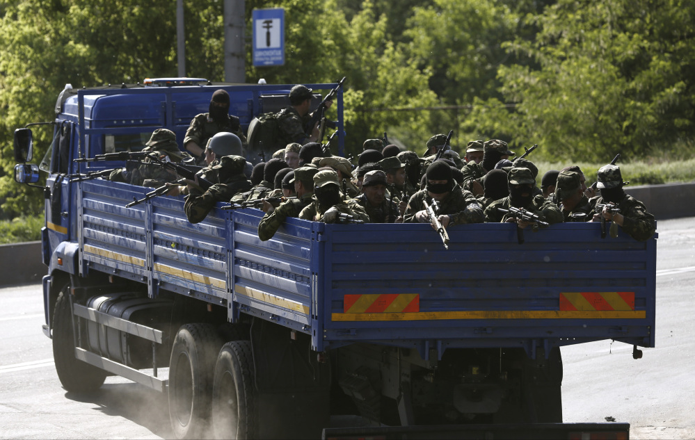 Pro-Russian militia arrive to take positions outside the airport in Donetsk, Ukraine.