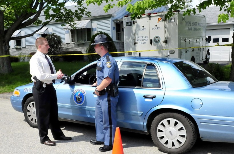 INVESTIGATION: Maine State Police Detective Sgt. Jeffrey Love, left, and trooper Randy Hall confer on Monday as investigators continue to search for evidence inside the Brooklyn Avenue home of Aurele Fecteau in Waterville.