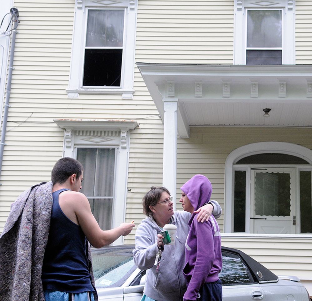 AFTERMATH: Jackie Nelson, center, hugs her granddaughter, Sabrina Moulton, the building's owner, on Tuesday, along with tenant Anthony Luczkowski, after an early morning fire forced them to evacuate the 11 Cedar Court apartment building.