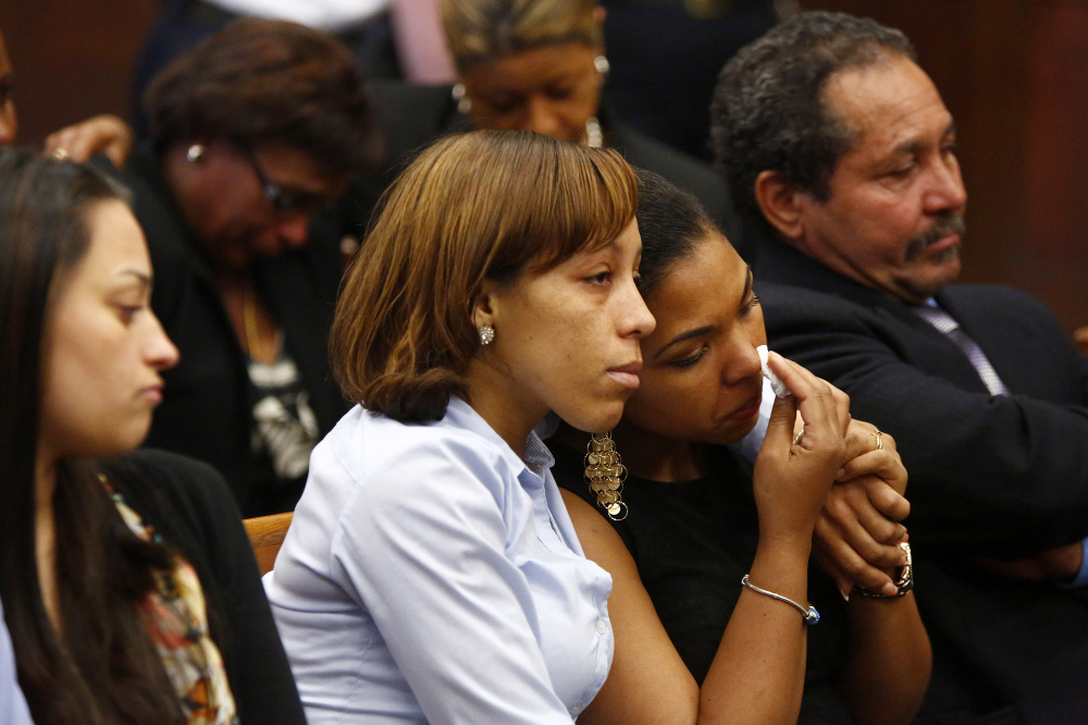 People identified by the district attorney as a victim's family members of react as they wait for former New England Patriots player Aaron Hernandez to appear at Suffolk Superior Court in Boston, Mass., on Wednesday, May 28, 2014. Hernandez is accused of gunning down two men he did not know in 2012 because one of them bumped into him while dancing at a Boston nightclub. Hernandez pleaded not guilty.