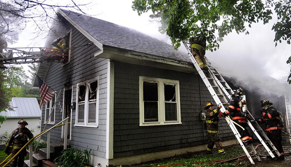 Fire response: Firefighters crawl through the second story window at a single-family Augusta home to extinguish a fire that heavily damaged the residence Wednesday. Firefighters from Augusta, Togus, Winthrop, Gardiner, Hallowell and Chelsea responded to the blaze reported just before 7 a.m.