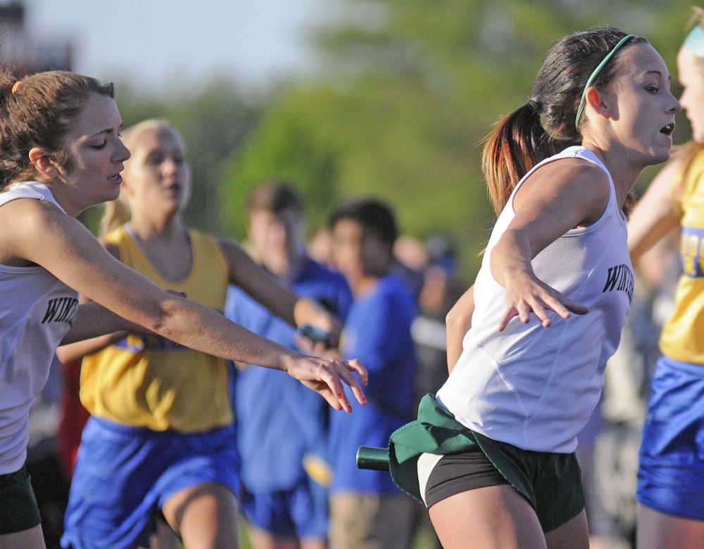 Staff photo by Andy Molloy Winthrop High School's Molly Kieltyka, right, grabs the bar from teammate Kaitlin Souza Thursday during the 4x4 relay.