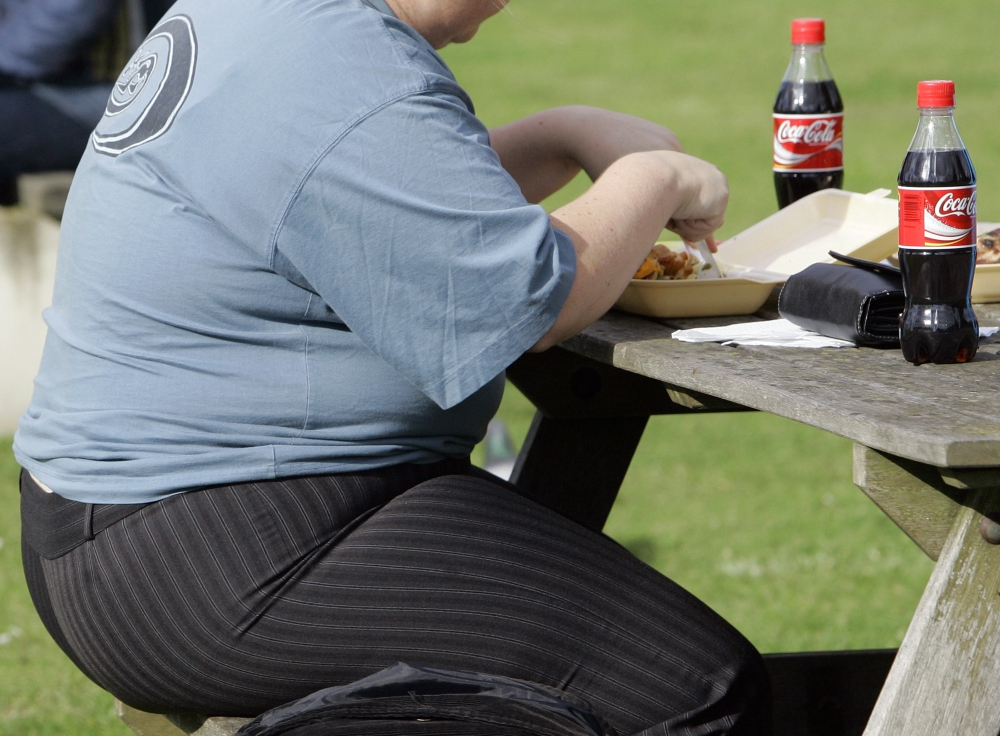 An overweight person eats in London. About two in three adults in the U.K. are overweight, making it the fattest country in Western Europe.