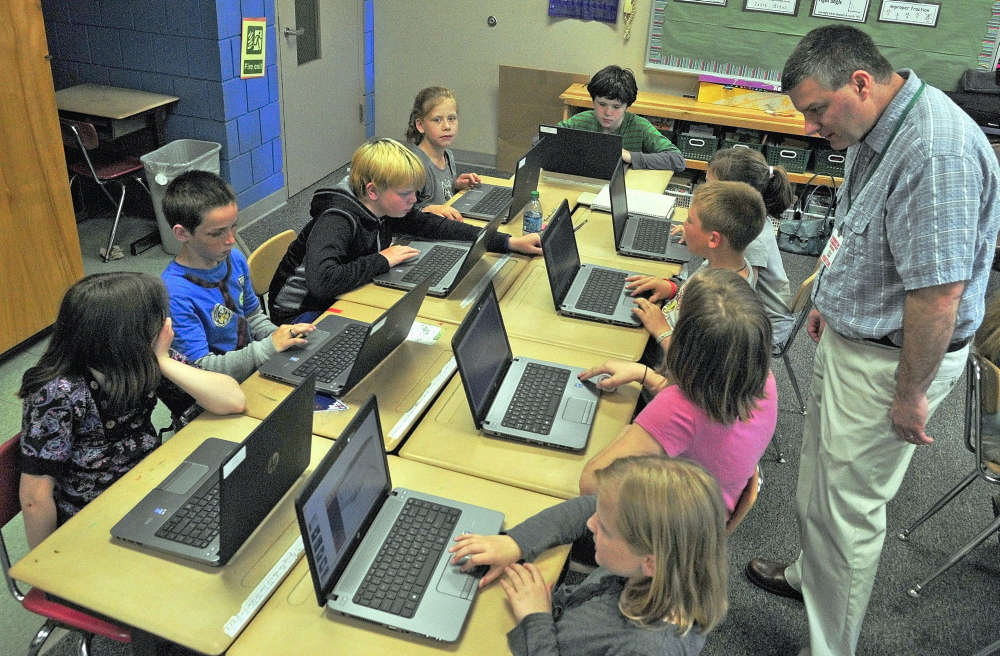 FIELD TRIP: Tony Paine, CEO of Kepware Technologies, right, chats with students during a visit on Friday, May 30 at Farrington School in Augusta. Paine's company donated laptops to the classroom earlier in the year.
