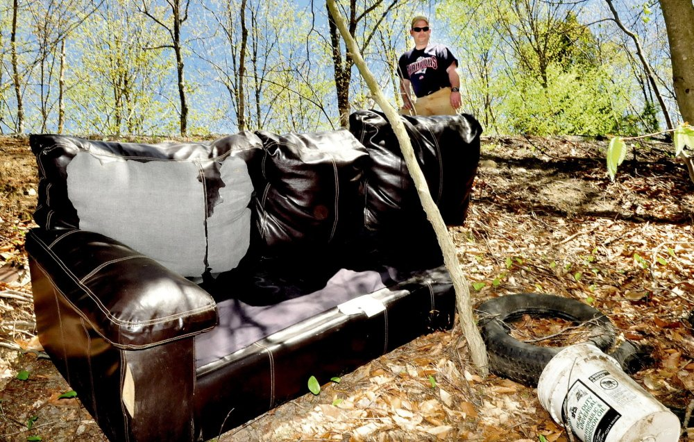 """WOODLAND HEADACHE: Gary Foss, facilities manager for the town of Belgrade, looks at trash including a couch, buckets and tires that were thrown in the woods off Penney road in Belgrade. """"This is unnecessary and irresponsible,"""" Foss said."""