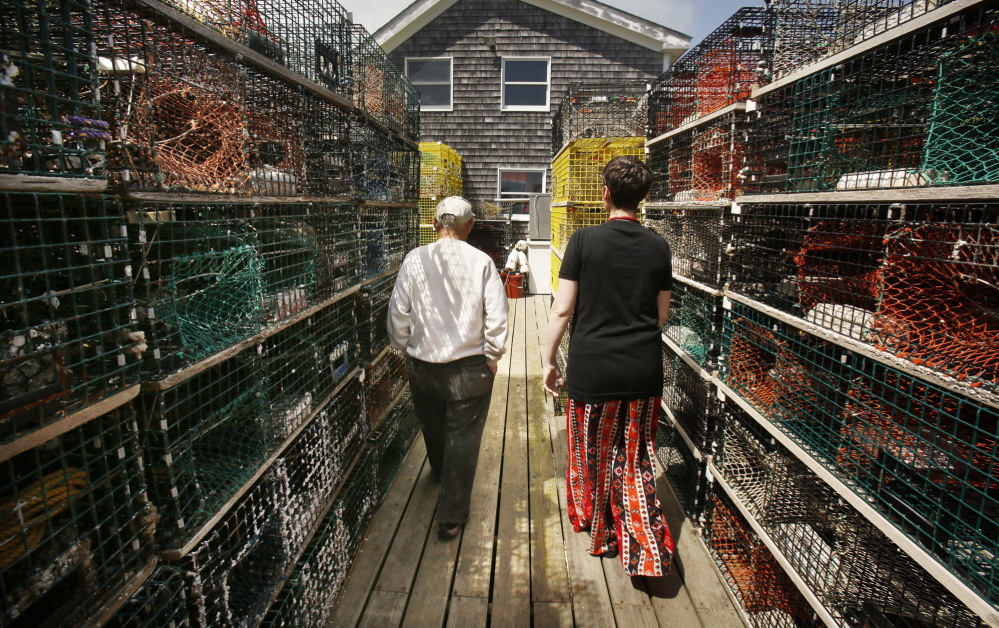 "Jennifer Desmond walks past lobster traps with Harold ""Sonny"" Warren on the dock at his Vinalhaven home last month. Desmond has a recreational lobster license and Warren, who is also a Korean War veteran, helps her haul her traps. ""He's my sternman,"" she said."