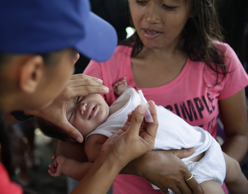 Red Cross and UNICEF medics administer polio and measles vaccinations to typhoon survivors after Typhoon Haiyan ravaged the city of Tacloban, Leyte province in central Philippines.