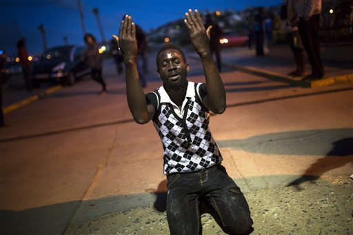 A sub-Saharan migrant prays in front of a temporary center for immigrants after scaling a fence that divides Morocco and the Spanish enclave of Melilla in North Africa.