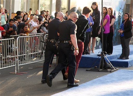 "Vitalii Sediuk is walked off in handcuffs after allegedly accosting Brad Pitt at Wednesday's premiere of ""Maleficent"" at the El Capitan Theatre in Los Angeles."