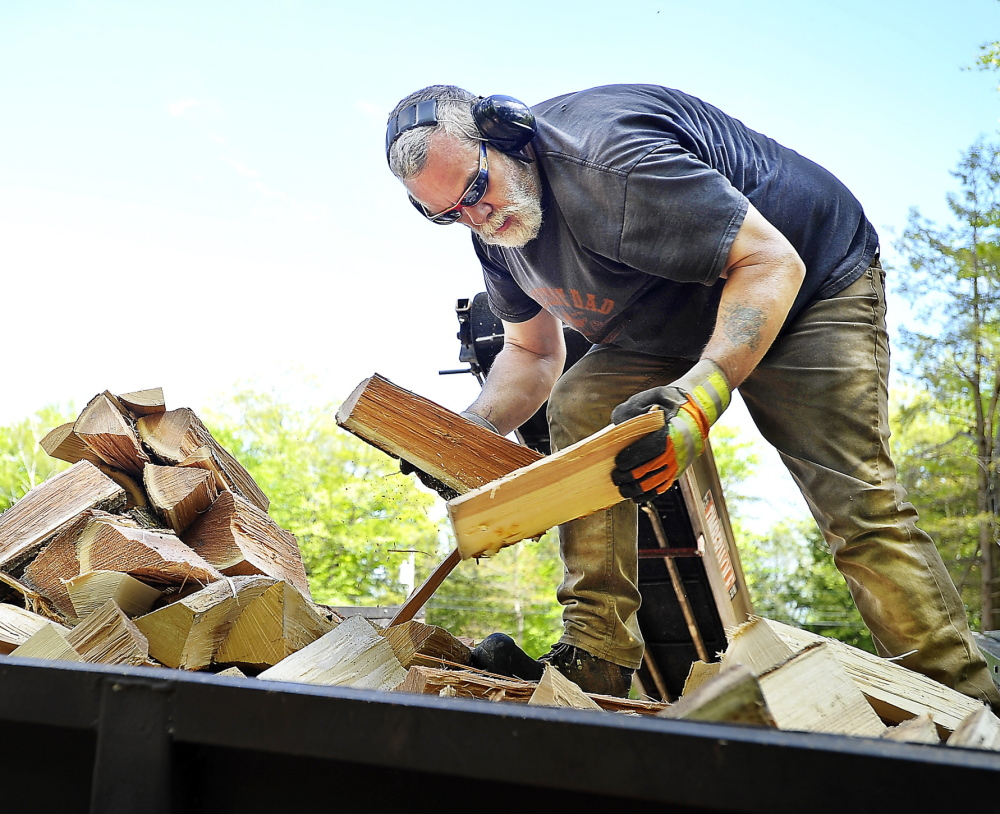 Mark Killinger, owner of Atlantic Firewood, arranges processed firewood in the bed of his truck in Windham. He and other dealers are receiving larger and earlier orders this year.