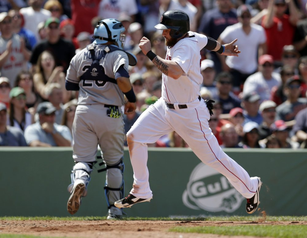 Boston Red Sox's Jonny Gomes, right, scores on a sacrifice fly as Tampa Bay Rays catcher Jose Molina, left, is unable to make the play in the fourth inning of a baseball game, Sunday, in Boston.