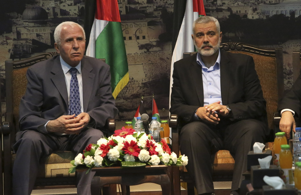 Gaza's Hamas Prime Minister Ismail Haniyeh, right, and senior Fatah official Azzam al-Ahmad meet in Gaza for talks aimed at reaching a reconciliation agreement between the two rival Palestinian groups, Hamas and Fatah in this April 2014 file photo.